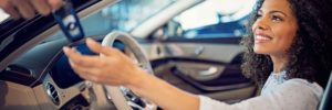 Car dealer handing keys to happy new car owner